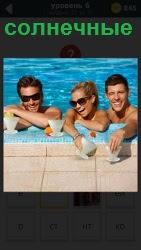 несколько молодых людей в воде в солнечных очках с коктейлем