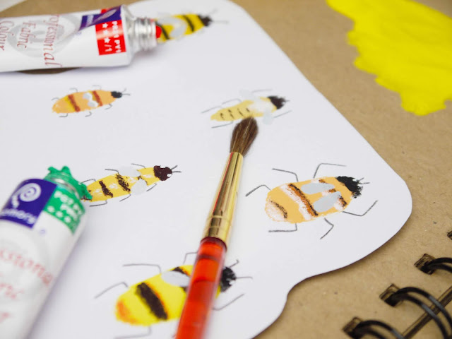 bee illustrations with brushes and tubes of paint