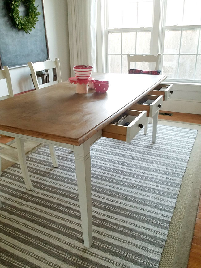 dining room with table with three drawers, white and grey striped rug and chalkboard with wreath on it.