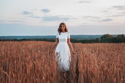 Chica vestida de blanco paseando por pasto de trigo