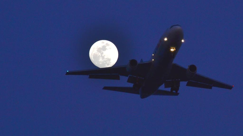 Plane lands under a full Moon