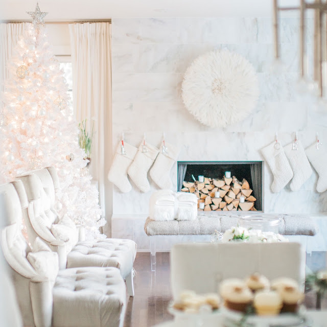 Living room marble fireplace with juju hat and white velvet stockings grey velvet chairs fluffy white flocked Christmas tree