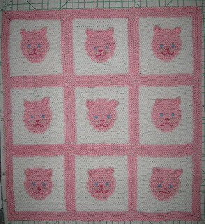 A square baby blanket made up of 9 squares, joined by pastel pink borders. Each square is white with a pastel pink circle in the middle. The circle is a kitten's face. Facial features are embroidered in blue yarn for the eyes and dark pink yarn for the nose and mouth. The ears are shaped like small triangles and stitched on to the surface of the blanket along the top edge of the pastel pink circles so that they can flap about. The blanket resembles a tic tac toe game except there are faces where the noughts and crosses should be and the entire blanket is finished off with a pastel pink plain border of solid crochet around the perimeter.