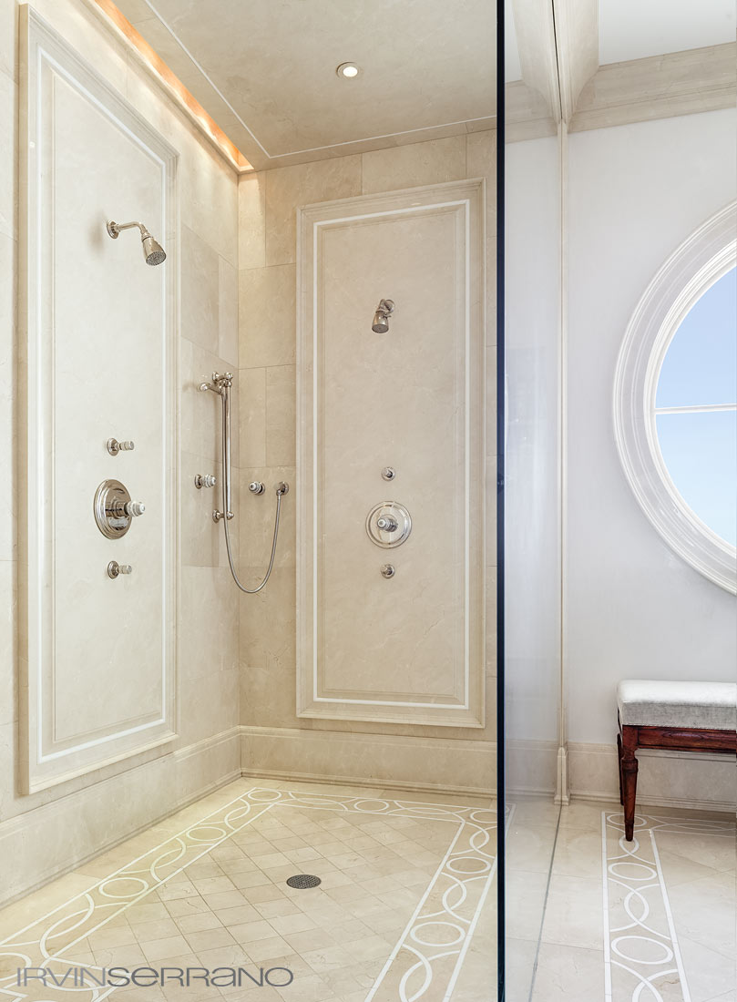 A master bathroom in a Southport Estate in coastal Maine features glass shower, marble flooring and
