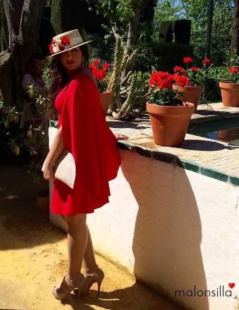 Chica en un jardin, de boda en Sevilla con look rojo, canotier y bolso malonsilla