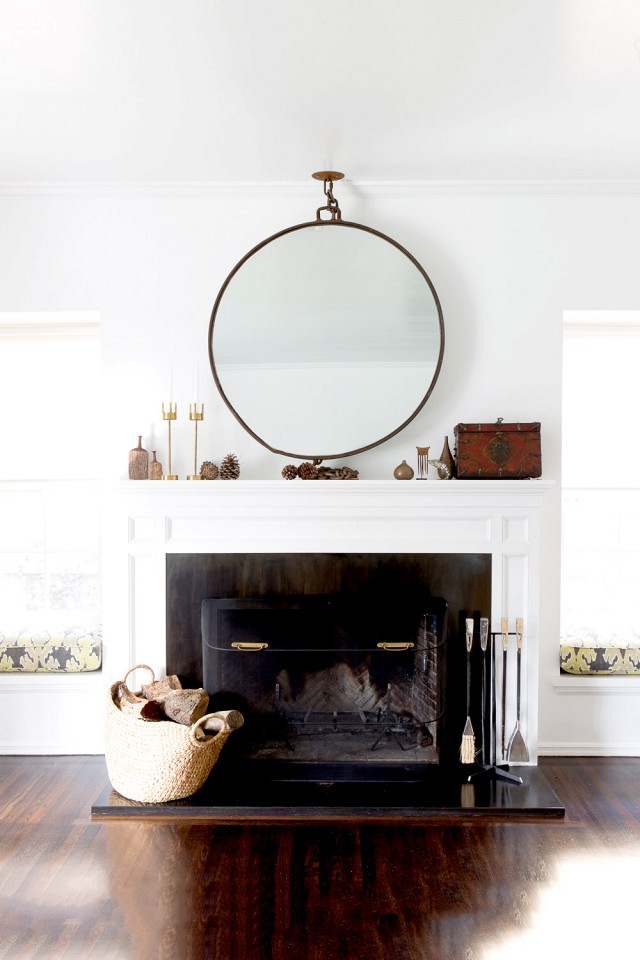 round statement mirror over fireplace