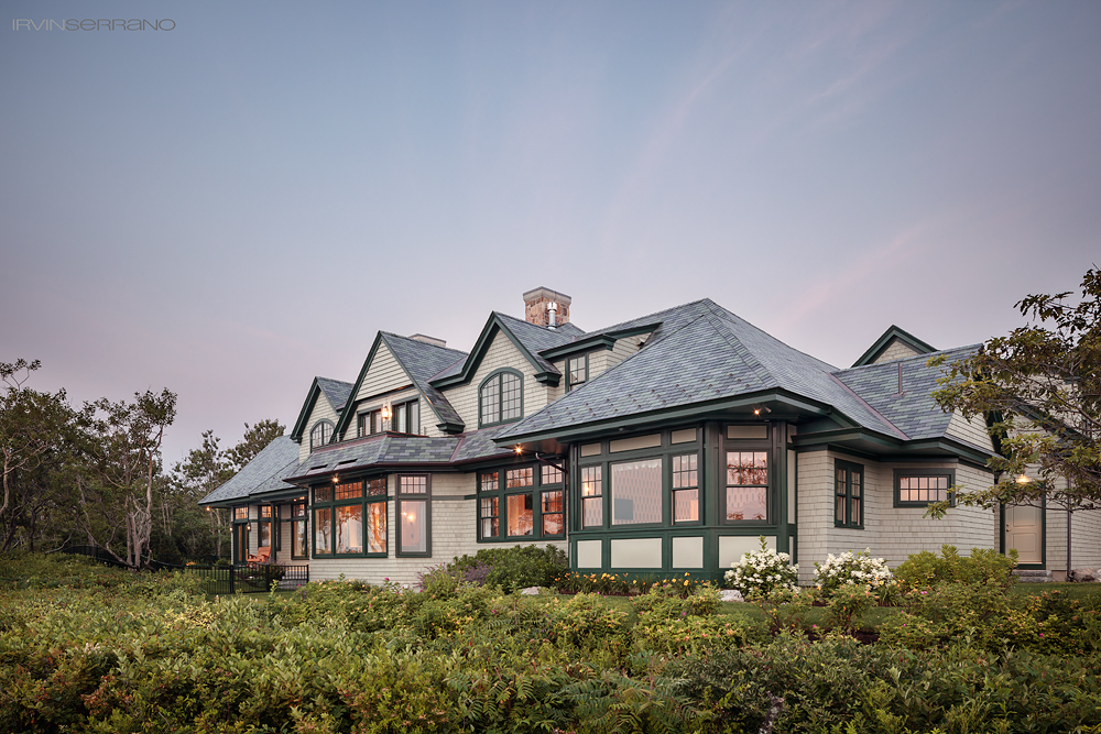 Exterior of the back of an oceanview home lit up at dusk in coastal Maine.