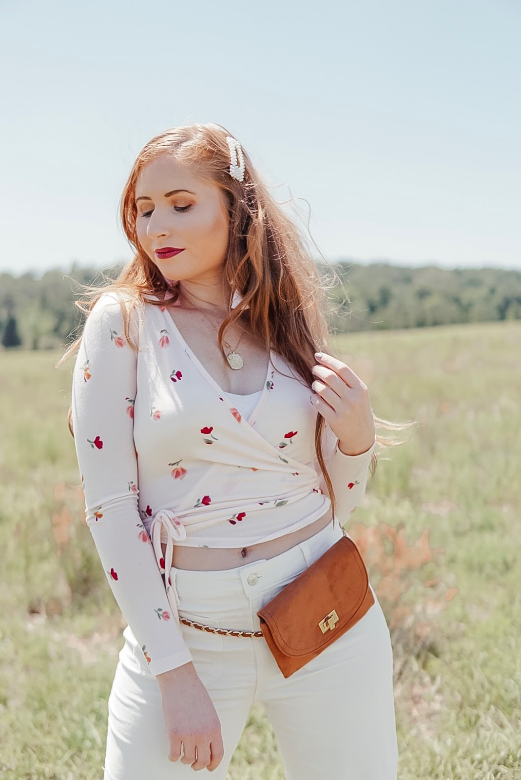 tampa blogger amanda burrows of affordable by amanda is wearing a florap wrap top and white corduroy jeans out in a wildflower field. she is wearing long extensions from barefoot blonde extensions in the color chestnut.