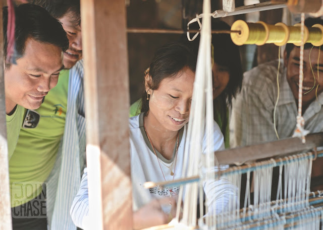 Members of NAG watch a local resident behind her wooden loom in Sagaing Division, Myanmar.