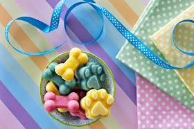 A bowl of colourful frozen dog treats with pastel polka dot napkins and ribbon