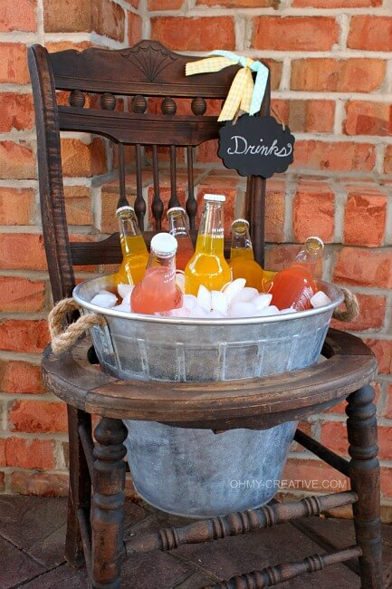 Old chair with a galvanized bucket in the seat area filled with ice and soda pop