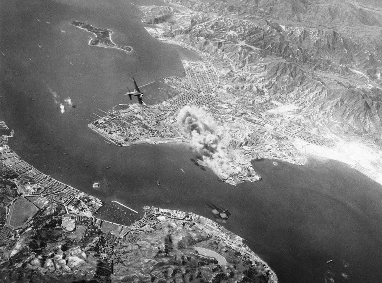 Smoke billows up from the Kowloon Docks and railroad yards after a surprise bombing attack on Hong Kong harbor by the U.S. Army 14th Air Force October 16, 1944. A Japanese fighter plane (left center) turns in a climb to attack the bombers. Between the Royal Navy yard, left, enemy vessels spout flames, and just outside the boat basin, foreground, another ship has been hit.