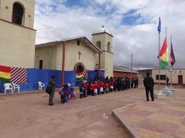 Eine 25 m große Flagge wurde vor der Pfarrkirche aufgehängt Davor sind auch Kindergartenkinder und Schüler angetreten.