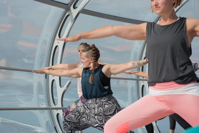 Yoga in the sky on the i360 with MyEscape and Nine Lives Yoga - Tess Agnew fitness blogger doing Warrior pose