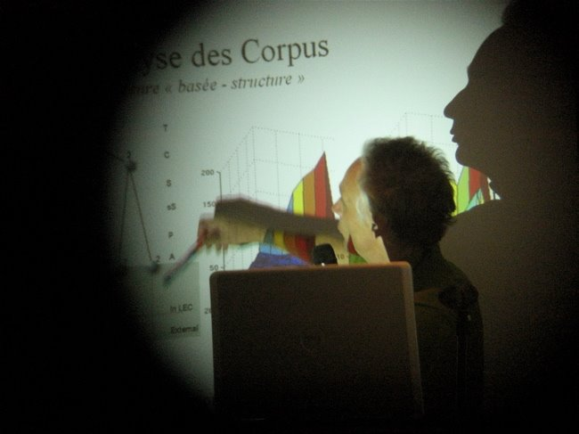 Blick durch ein Opernglas auf Redner an einer PowerPointPräsentation
