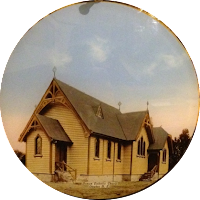 A wooden church with steep green roof. St Joseph's Catholic Church, yellowish