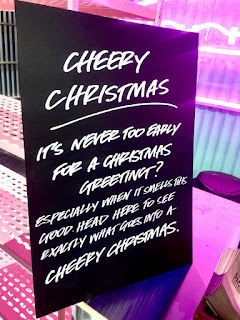 A big black board with Cheery Christmas in informal white font on a bright background.