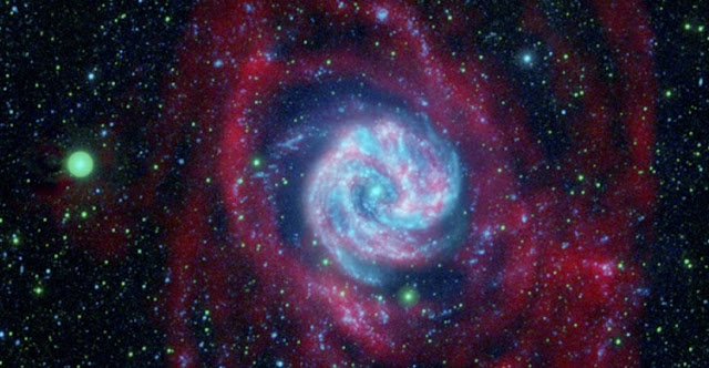 RIT researchers propose that the outer gas disk of spiral galaxies could be teeming with black holes that emit gravitational waves as they collide. Shown here is the Southern Pinwheel galaxy seen in ultraviolet light and radio wavelengths. The radio data, colored here in red, reveal the boondocks of the galaxy where orbiting black holes might exist. Credit: NASA/JPL-Caltech/VLA/MPIA