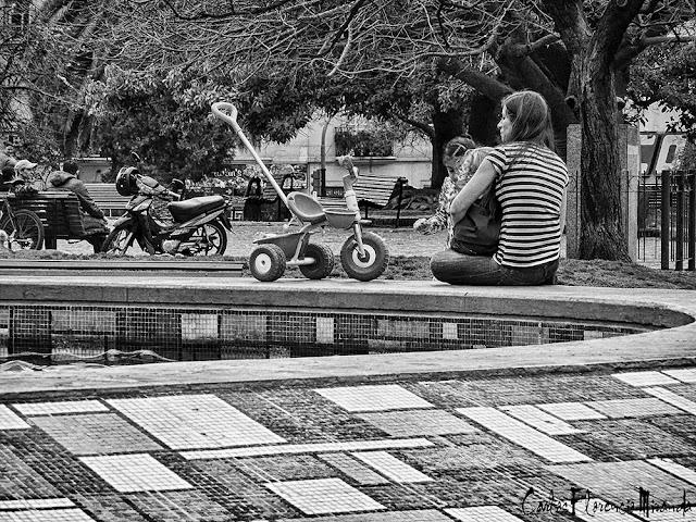 Blanco y Negro Una madre sentada en borde de pileta con nena en brazos.