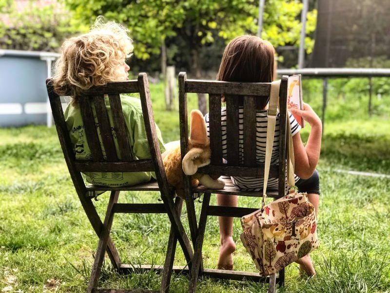 Crianças sentadas num jardim