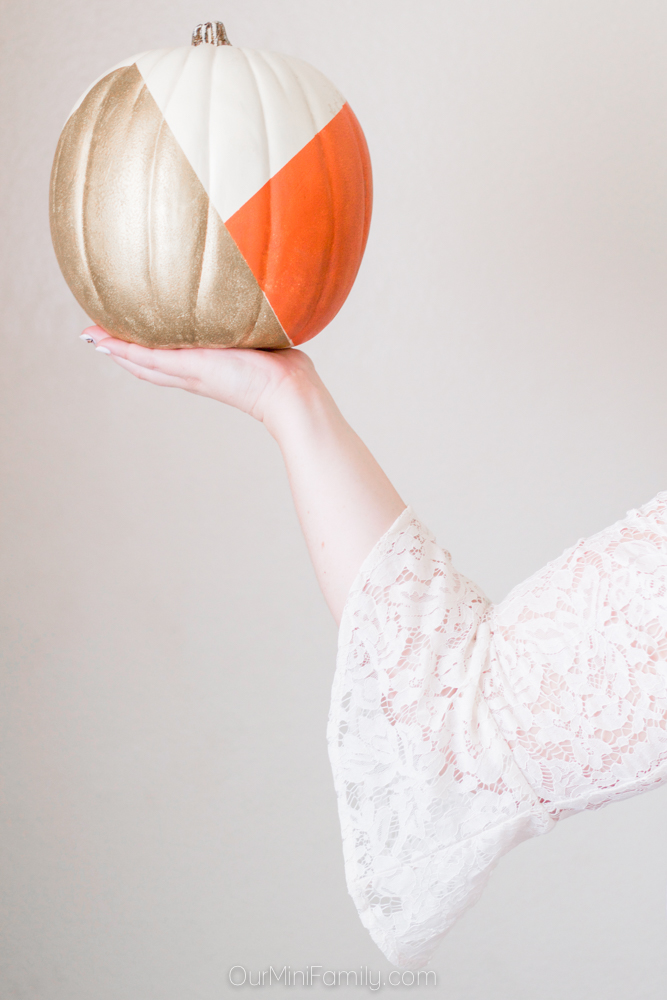 woman hand holding up gold painted pumpkin