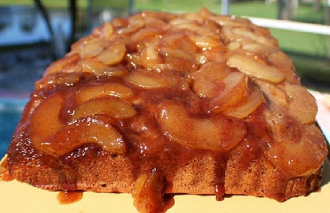 This is a semi homemade caramel apple cake in a 13 x 9 pan.. The cake has caramel on the bottom made baked in the pan with fresh apple slices and the cake is baked on top of the apple caramel syrup. It is on a plate that the caramel while hot is dripping onto the cake.