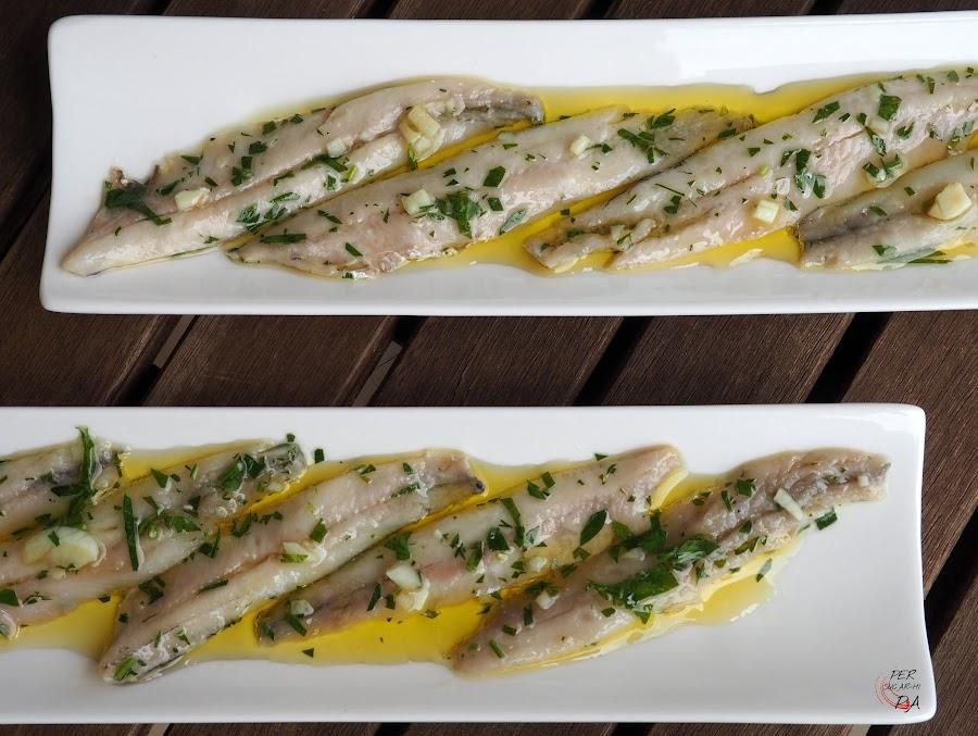 Boquerones, limpios y en lomos, marinados en vinagre y servidos con una picada de ajo y perejil con aceite de oliva