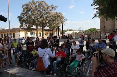 Personas de diferentes edades escuchan de pie y sentados en sillas de ruedas.