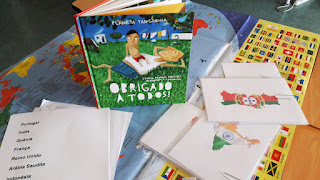 """Cartões com a representação de vários países espalhados em cima de uma mesa e o livro """"Obrigado a todos!"""""""