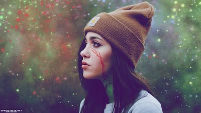 Chica con gorra y tatuaje en la cara mirando a la nada