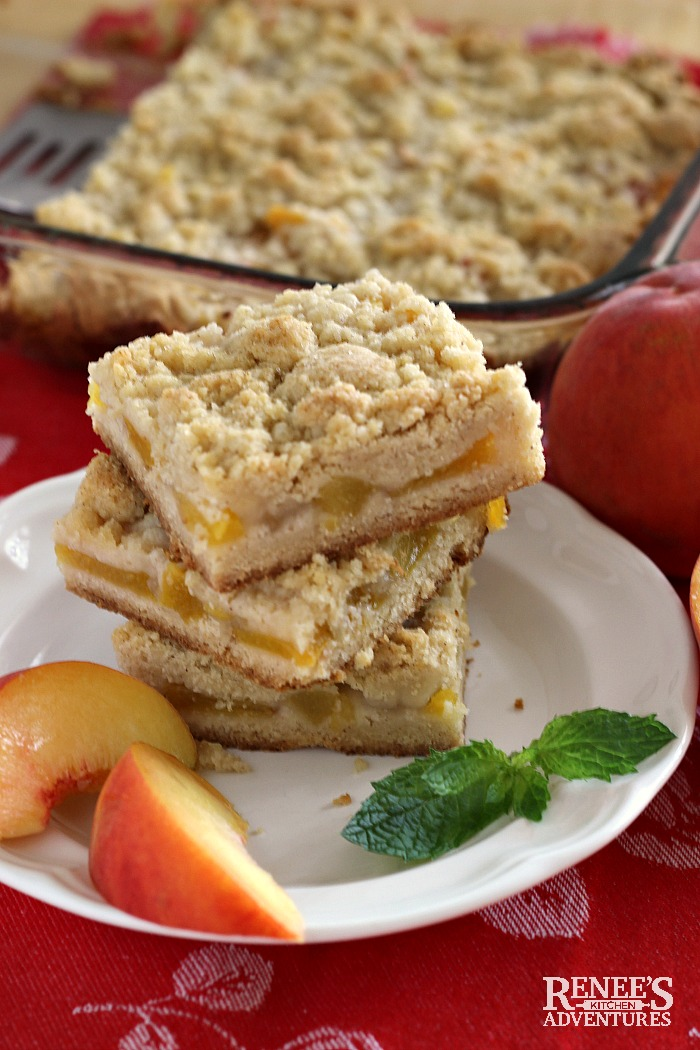 Easy Peach Crumb Bars stacked on a plate with pan of Easy Peach Crumb Bars in background
