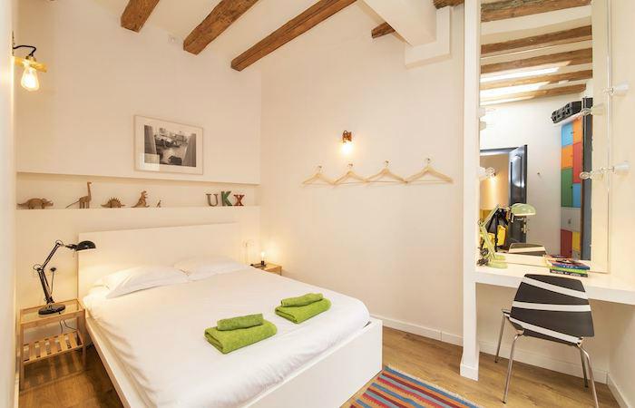 Cómo decorar un apartamento joven con poco dinero: Dormitorio de techos altos, vigas de madera y tocador moderno