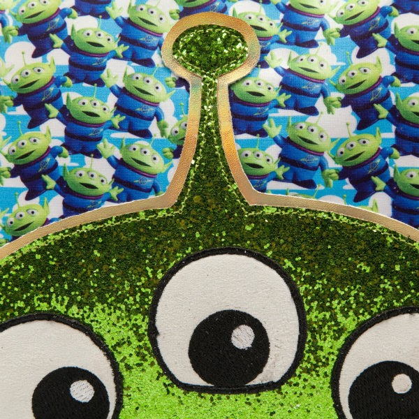 close up of green glitter alien face with embroidered eyes on front of clutch bag