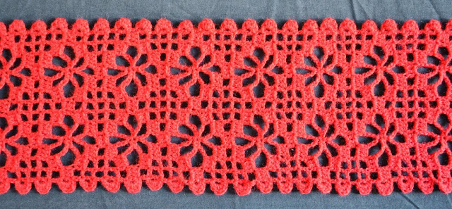 Close-up of a red spider stitch scarf that I completed in January 2015.  The large holes are part of the spider stitch design. The smaller holes are part of a filet grid.  The border pattern uses bumpy shapes..