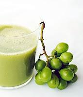 Bir bardak yeşil renkli koruk suyu ve yanında küçük bir salkım ekşi ham üzüm