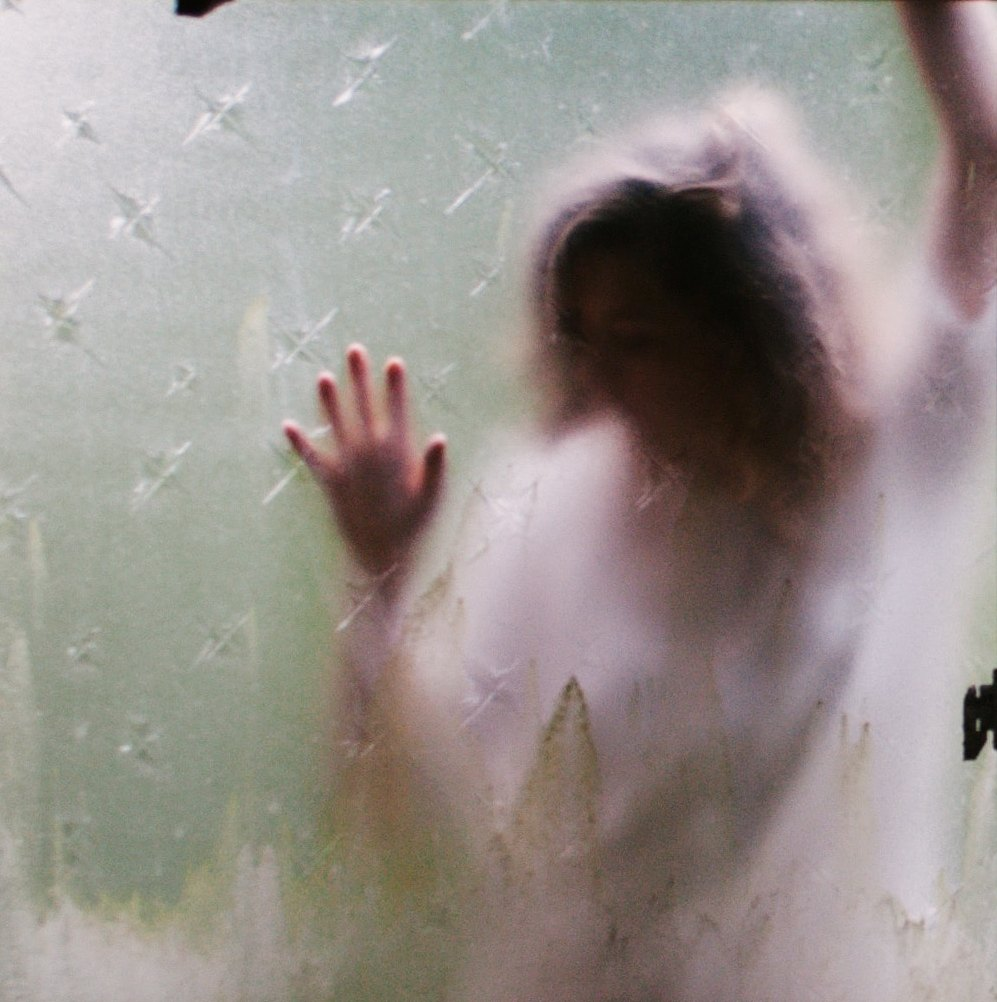 A photo taken from inside a building of a girl leaning up against a dirty, frosted window from outside - the side of her head pressed onto the window, as are her right hand, while her left arm is up against it as she reaches upwards, hand outside view of the window