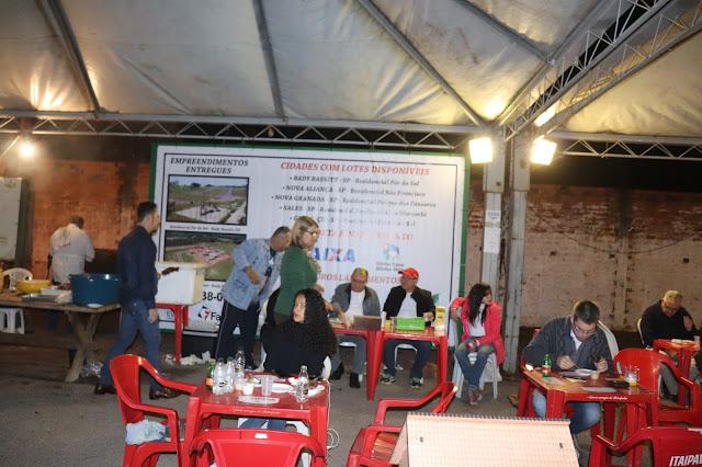 Voluntários montam barraca para servir espetinhos de carne em prol do Lar Moisés Natalino