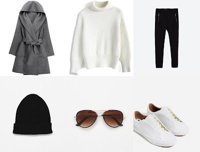 casaco comprido cinzento claro, calças pretas. tênis brancos, óculos de sol em massa e gorro preto
