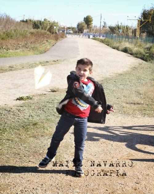 Niño lanzando un avión de papel