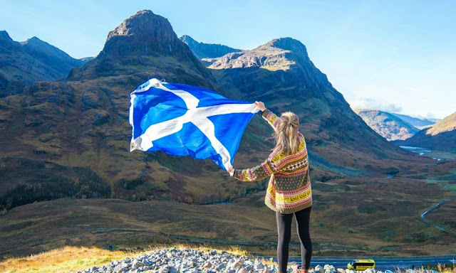 Girl holding Scottish saltire flag in front of Highlands mountains