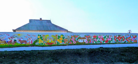 Петріківка. Центр народного мистецтва «Петріківка». Розписаний паркан на трасі Р-52