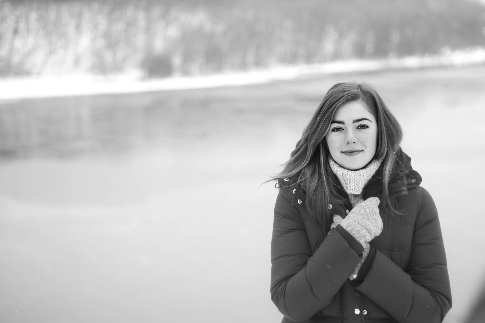 冬の川辺で両手を胸の前に交差させながら佇む女性