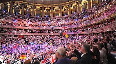 The Royal Albert Hall in London is the venue for the Last Night of the Proms, Image contains thousands of people inside the Hall, there are lots of flags and streamers being waved by a colorful crowd from the floor  up through several levels of balconies.