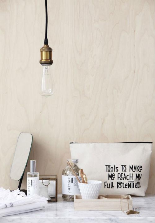 Eine Glühbirne mit Messingfassung hängt im Bad über einem Regal mit Accessoires