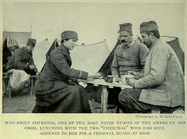 """MISS EMILY SIMMONDS, ONE OF THE MOST NOTED NURSES OF THE AMERICAN RED CROSS, LUNCHING WITH THE TWO """"CHEECHAS"""" WHO HAD BEEN ASSIGNED TO HER FOR A PERSONAL GUARD AT BROD"""