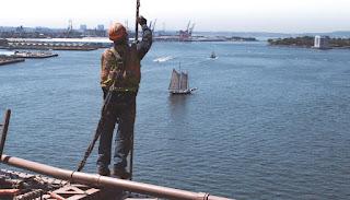 Ouvrier oeuvrant au-dessus du port, chaloupe ancienne