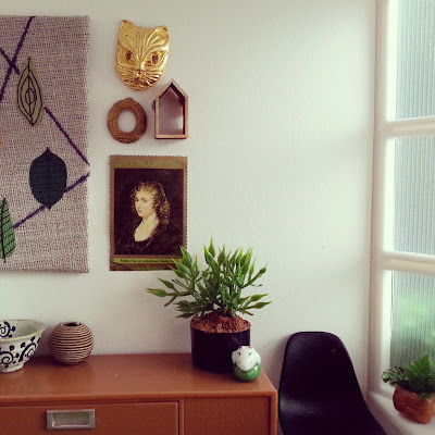 One-twelfth scale modern miniature office scene containing a credenza with a black Eames chair next to it and an artwork with leaves above it. On the credenza is a bowl, a vase, a potted plant and a ceramic ornament. On the windowsill to the right is a potted plant.