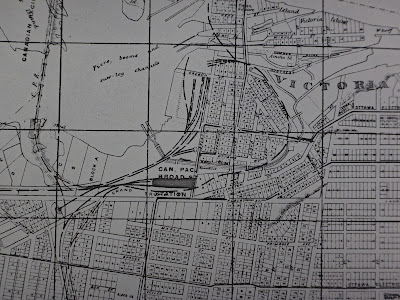 Photo of a section of a 1913 map of the City of Ottawa with extents Bay Street (East), Somerset Street (South), Bayview Road/Bayswater (West), and Ottawa River/Chaudière Island (North). Nearly all blocks are shown subdivided, most with numbered parcels. The Canada Atlantic Railway line coming up from the south into LeBreton Flats is drawn overtop the divided lots, leading to the Can. Pac. Broad St. Station and continuing past to circumavigate the east side of LeBreton Flats.