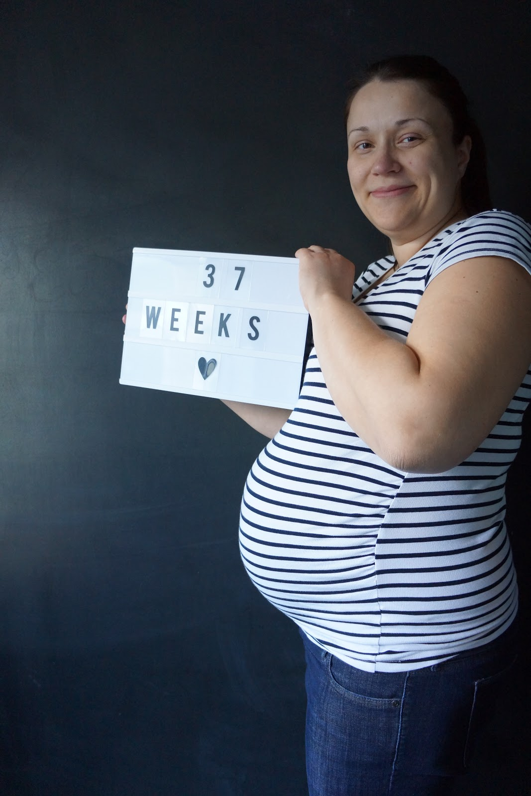 mum holding a light box with 37 weeks written on it