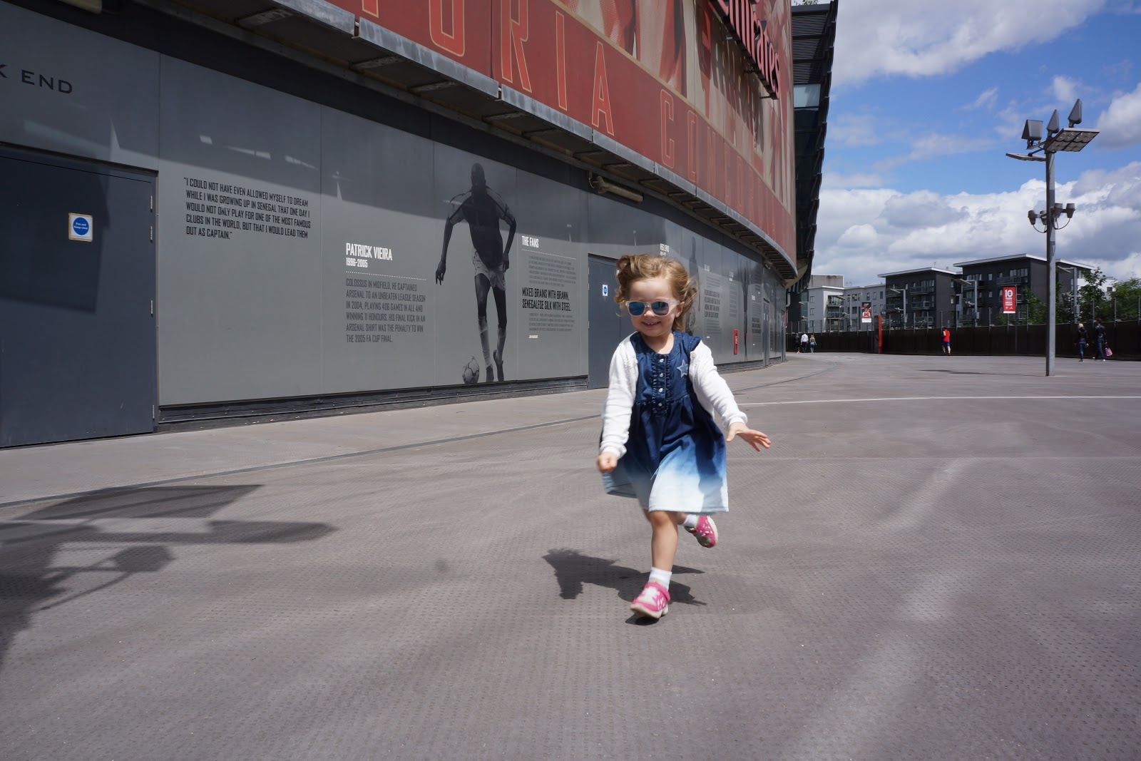 girl running outside Arsenal Stadium